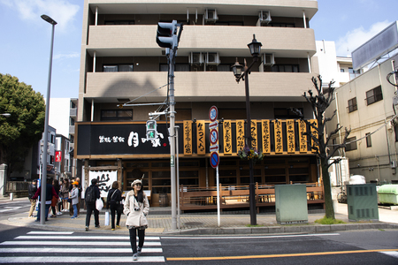 Tokyo, Japan - March 31, 2019 : Japanese and foreigner people walking crossing road at junction of Naritasan Omote Sando or Narita old town with traffic at Chiba Prefecture Фото со стока - 130764449
