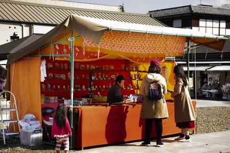 Tokyo, Japan - March 31, 2019 : Japanese people and foreigner travelers playing shooting game in street market festival at Naritasan Shinshoji of Narita at Chiba Prefecture Редакционное