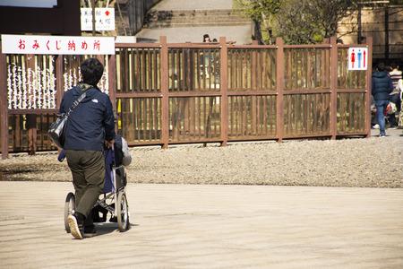 Tokyo, Japan - March 31, 2019 : Japanese family people push wheelchair and bring oldman father walking visit and praying in Naritasan Shinshoji Temple at Chiba Prefecture