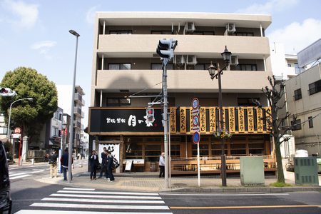 Tokyo, Japan - March 31, 2019 : Japanese and foreigner people walking crossing road at junction of Naritasan Omote Sando or Narita old town with traffic at Chiba Prefecture Фото со стока - 130764537