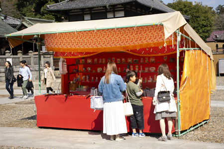 Tokyo, Japan - March 31, 2019 : Japanese people and foreigner travelers playing shooting game in street market festival at Naritasan Shinshoji of Narita at Chiba Prefecture on March 31, 2019 in Tokyo, Japan