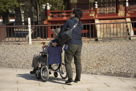 Tokyo, Japan - March 31, 2019 : Japanese family people push wheelchair and bring oldman father walking visit and praying in Naritasan Shinshoji Temple at Chiba Prefecture on March 31, 2019 in Tokyo, Japan