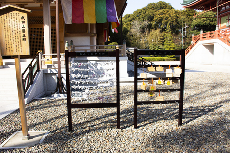 Tokyo, Japan - March 31, 2019 : Predicted paper for answer fortune not good and japanese and foreigner people tied and drop at Naritasan Shinshoji Temple at Chiba Prefecture on March 31, 2019 in Tokyo, Japan