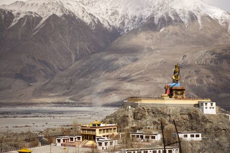Landscape and sandstorm cyclone with 32 metre statue of Maitreya Buddha near Diskit Monastery facing down the Shyok River towards Pakistan at nubra village at Leh Ladakh in Jammu and Kashmir, India