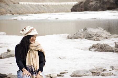 Travelers thai woman travel visit and posing portrait for take photo at view point of Confluence of the Indus and Zanskar Rivers while winter season at Leh Ladakh in Jammu and Kashmir, India Фото со стока