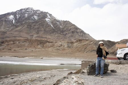 Travelers thai woman travel visit and posing portrait for take photo at view point of Confluence of the Indus and Zanskar Rivers while winter season at Leh Ladakh in Jammu and Kashmir, India