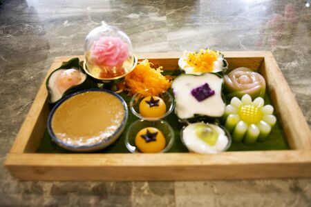 Nine auspicious thai desserts and many sweets snacks thai style for travelers people eating at restaurant cafe in Samut Songkhram, Thailand
