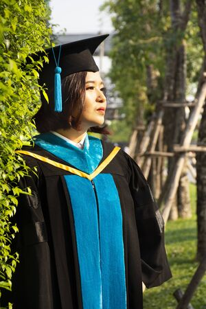 Thai women student wear graduation gown of Master Degree posing and portrait for take photo in commencement day of graduation ceremony in university at Nonthaburi city at Bangkok, Thailand