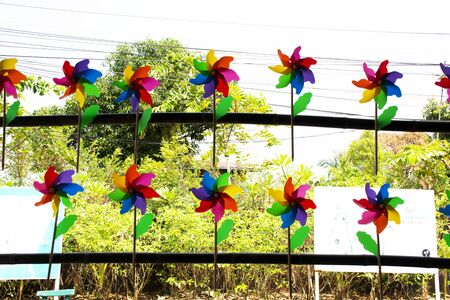 Colorful pinwheel and windmill toy made from plastic bottle recycle in garden at outdoor in Thailand Foto de archivo
