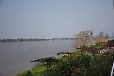 Thai people worker build bamboo boat in the festival of Illuminated Boat Procession or Lai Reua Fai and travelers people looking and join event at riverside of Mekong river in Nakhon Phanom, Thailand