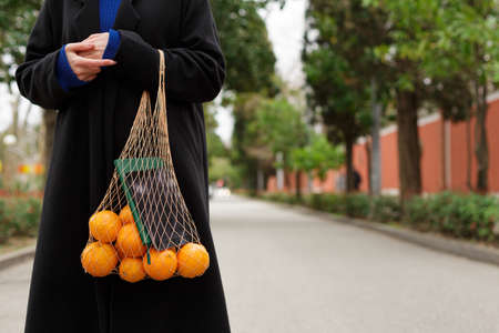 A girl holds a string bag with oranges and a notebook standing on the street 版權商用圖片
