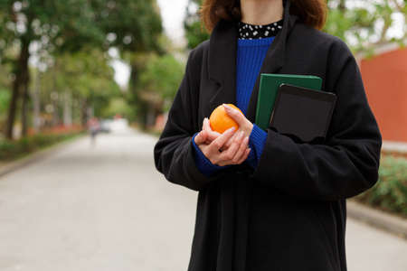 A girl holds a string bag with oranges and a notebook standing on the street Stock Photo