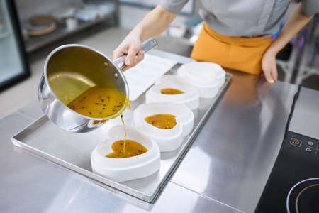 A bright girl cooks sweet dishes at a small production facility Archivio Fotografico
