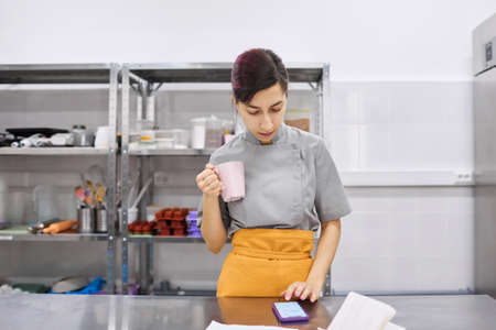 Pastry chef girl checks the Internet news feed and drinks coffee