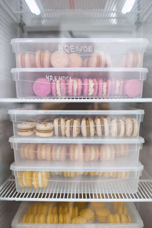 Colorful macaroons in transparent boxes are stored in the refrigerator