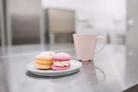 A cup of hot coffee and a saucer of bright macaroons on the table