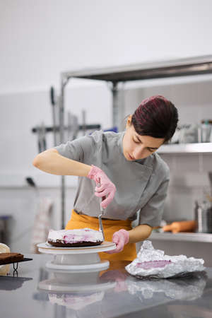 A pastry chef girl is engaged in the preparation of a cake