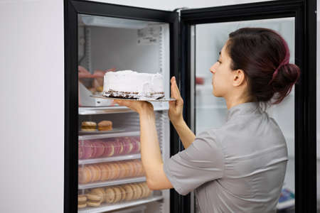 A pastry chef puts the finished cake in the refrigerator Archivio Fotografico