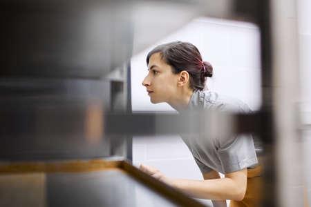 Stylish pastry chef checks the readiness of the dish in the oven Archivio Fotografico