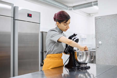 Pastry chef girl prepares fresh cakes at her small production facility Archivio Fotografico