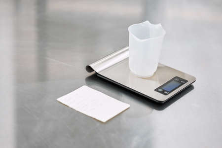 A silver electronic scale sits on the kitchen table