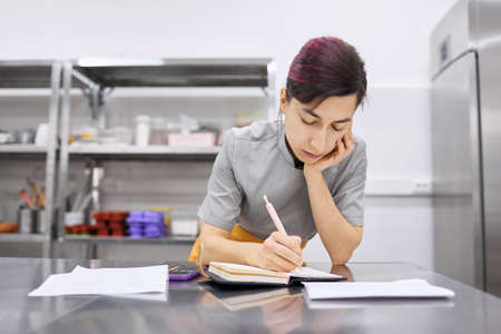 The pastry chef girl makes notes in a notebook.
