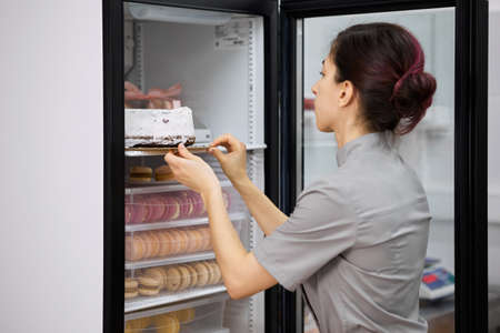 A bright pastry chef puts the finished cake in the refrigerator