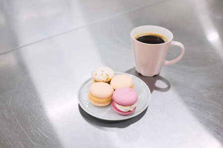 A cup of hot coffee and a saucer of bright macaroons