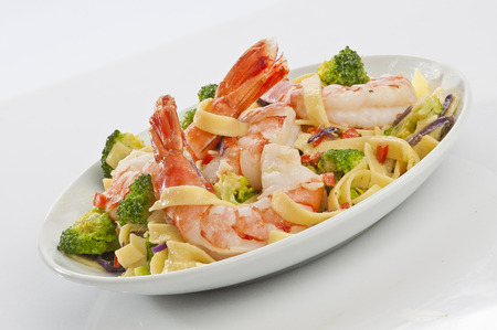 Jumbo Shrimp Pasta with broccoli & Vegetable with cheesy white gravy on white plate with white background