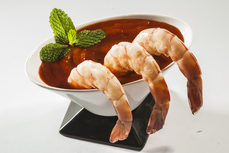 Cooked Jumbo shrimps with tomato salsa and mint with fork on white background