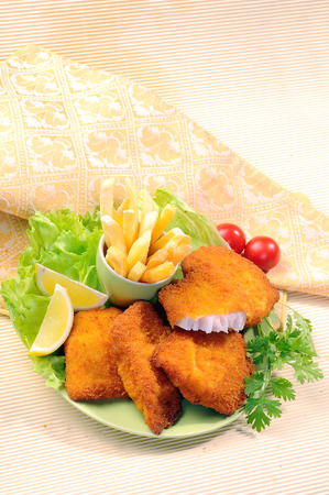 Breaded Fried fish with potato fries and tomato ketchup with lemon cherry tomato Stock Photo