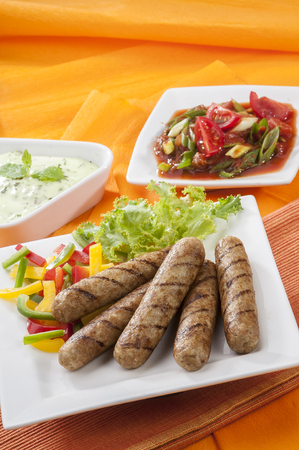 Chicken Seekh Kebabs with letus coloured bell pepper with tomato onion pickle and yogurt herb dip on white plates and on orange background