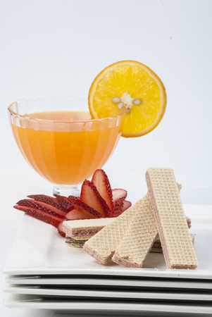 Wafer biscuit with orange juice orange slice cherry on toothpick on white plate on white background