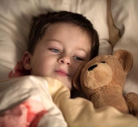 niño durmiendo: Muchacho lindo en la cama con el oso de peluche Foto de archivo