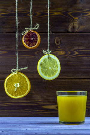 Hanging on threads slices of lemon, orange and lime. Summer fresh, glass of orange juice