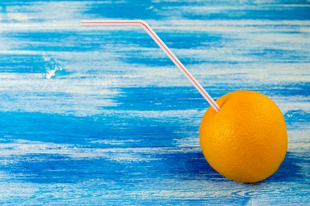 Ripe orange with tube for cocktail on the blue background. Summer drinks