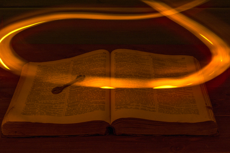The open Holy Bible is on the table. Ancient key. A fire flying over the Bible illuminates its pages. Religion