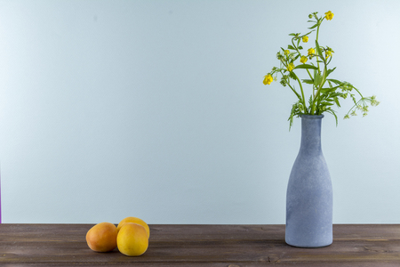 Apricots are on a wooden table. Vase with wildflowers on a blue background.