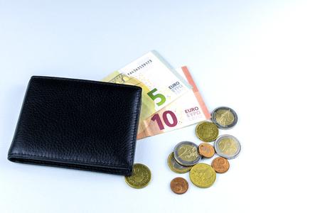 A few Euro bills are in the men's purse. Near are a few coins. Cash