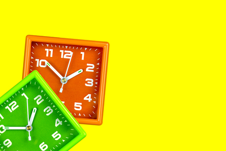Two bright alarm clocks on a yellow background. Table alarms green and orange