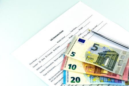 Life insurance form. A few pills and bills on the sheet. Cash banknote euro. Blue background