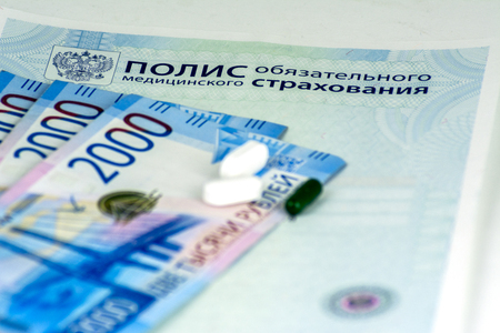 Close-up of Russian health insurance policy, Russian cash banknotes and a few pills on blue background