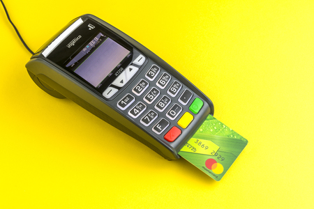 Moscow, Russia, 13.11.2018. Credit card payment terminal on yellow background. Green Plastic card Mastercard inserted into the terminal