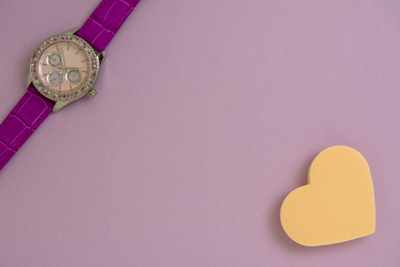 Beautiful womens wrist watch and heart shaped makeup sponge on purple paper background.