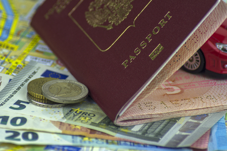 The concept of auto travel, passport, model of a red car. Cash money 5, 10, 20 euros on the background of the map