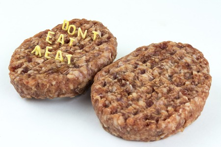 Raw Burger. The inscription of the letters curly pasta - do not eat meat on white Stock Photo