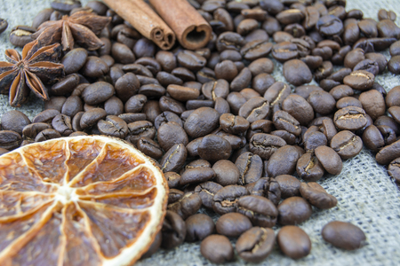 Coffee beans, cinnamon sticks scattered on the burlap. Slice of lemon.