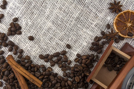 Coffee beans, cinnamon sticks and a coffee grinder on an old burlap Standard-Bild