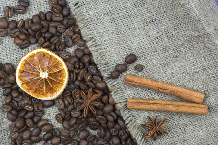 Coffee beans slice of lemon and cinnamon sticks are on the old linen fabric Stok Fotoğraf