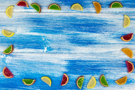 Multi-colored marmalade in the form of citrus slices laid out as a frame on an blue Board Banco de Imagens